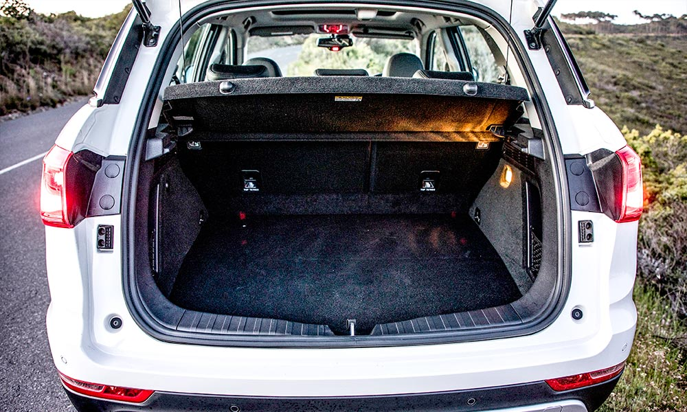 High-mounted boot board and low tonneau cover hamper luggage space.