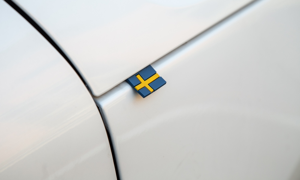 A Swedish flag peeks out from the bonnet crease.