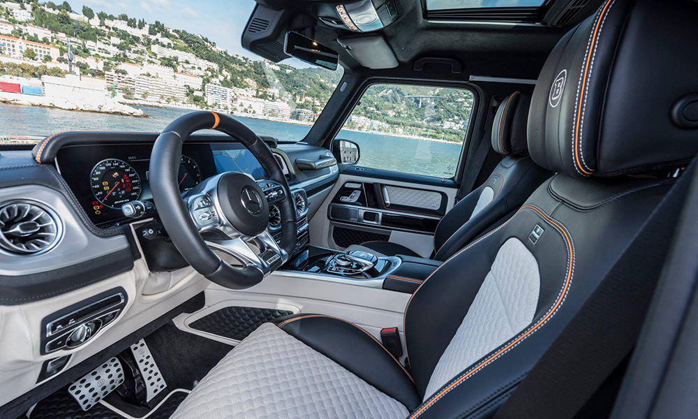 The model seen here features a two-tone leather interior, orange piping and contrast stitching. Notice the Brabus moniker quilted in the headrests.